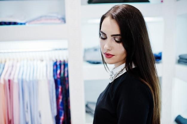 Fille brune magnifique dans la boutique de magasin de vêtements à la robe noire.