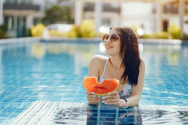Fille brune, manger des fruits au bord de la piscine