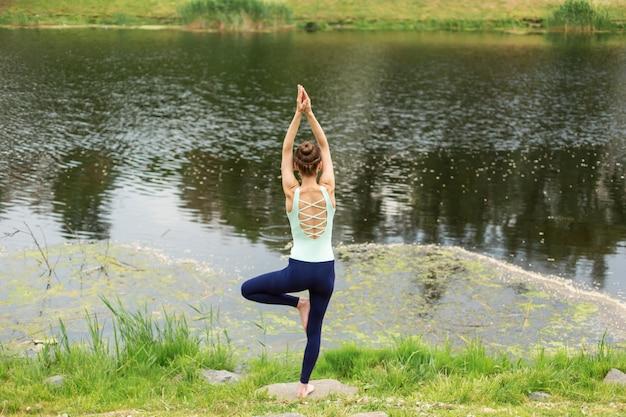 Fille brune mince, faire du yoga en été sur une pelouse verte au bord du lac