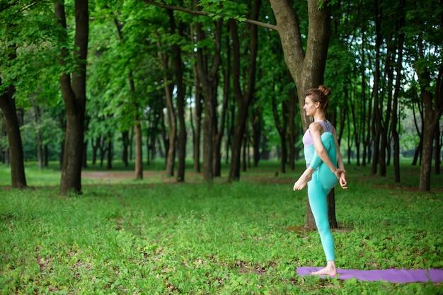 Fille brune mince fait du sport et effectue des poses de yoga belles et sophistiquées dans un parc d'été