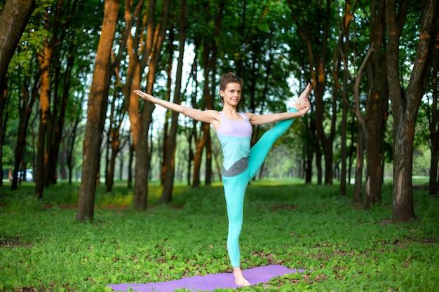 Fille brune mince fait du sport et effectue des poses de yoga belles et sophistiquées dans un parc d'été.