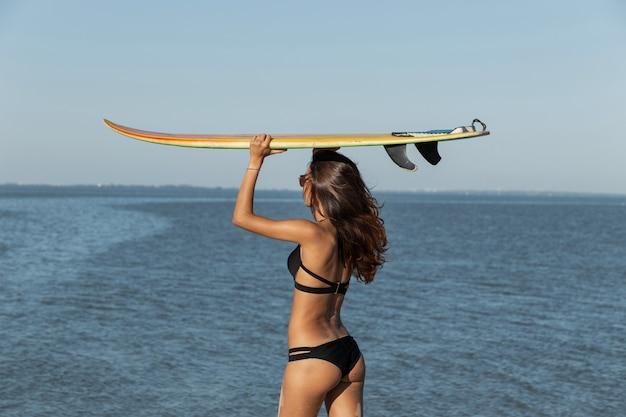 Une fille brune mince en maillot de bain noir tient une planche de surf jaune au-dessus de sa tête près de la mer par une journée ensoleillée