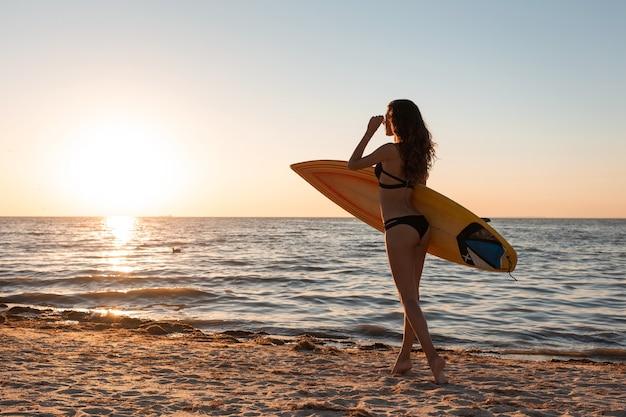 Une fille brune mince en maillot de bain se promène sur la plage de sable près de la mer au coucher du soleil et tient une planche de surf.