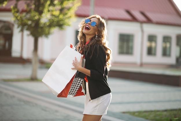 Fille brune à la mode avec des sacs à provisions en papier coloré, marchant dans la rue.