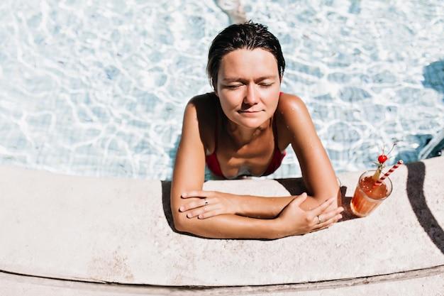 Fille brune se faire bronzer dans la piscine. femme bronzée se détendre dans l'eau avec un cocktail.
