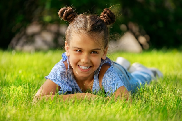 Une fille brune se trouve sur l'herbe dans le parc et sourit. photo de haute qualité