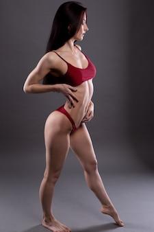 Fille brune sexy avec un corps parfait et de beaux cheveux longs, fille en sous-vêtements rouges
