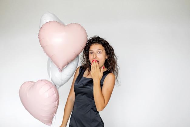 Fille brune sexy posant avec des ballons en forme de coeur sur fond blanc.