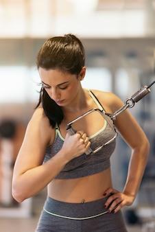 Fille brune soulevant des poids et travaillant sur ses biceps