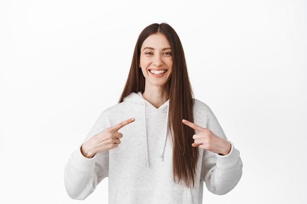 Une fille brune souriante et joyeuse se montre, montre le logo au centre, des dents de sourire blanches parfaites, auto-promotionnelle, debout contre un mur blanc