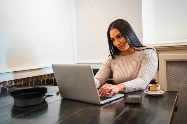 Fille brune télétravaillant dans un café avec ordinateur portable