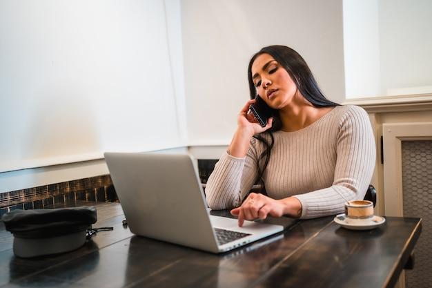 Fille brune télétravaillant dans une cafétéria avec ordinateur portable, faisant un appel professionnel