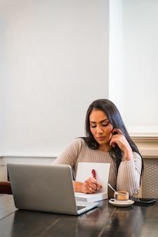 Fille brune télétravaillant dans une cafétéria avec ordinateur portable, prenant des notes lors d'une réunion en ligne, photo verticale