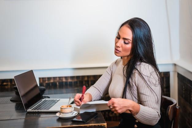Fille brune télétravaillant dans une cafétéria avec ordinateur portable, prenant des notes lors d'une réunion en ligne