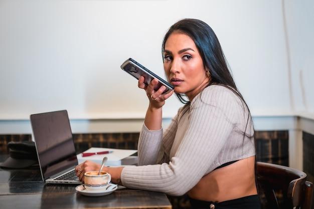 Fille brune télétravaillant dans une cafétéria avec son ordinateur portable, envoyant un message audio à un collègue