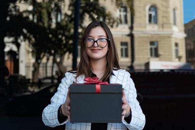 Une fille brune vous offre un cadeau. boîte noire avec arc rouge dans les mains des femmes. une jeune femme souriante dans des verres tient un cadeau dans ses mains.