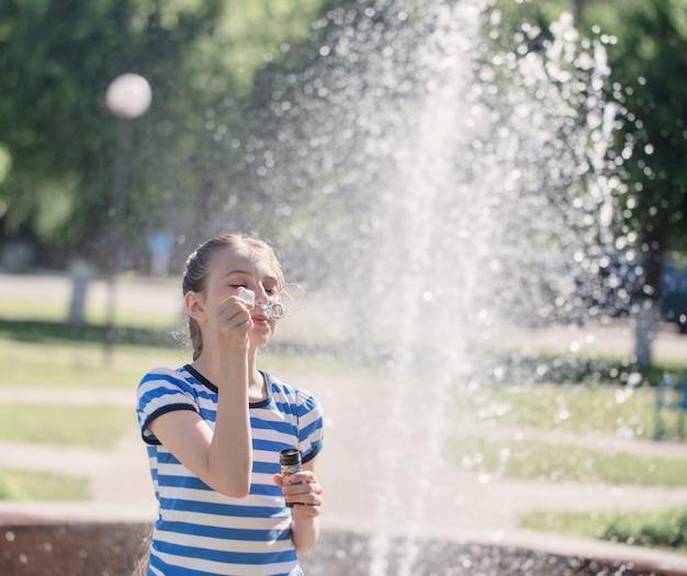 Fille avec bulle de savon en plein air