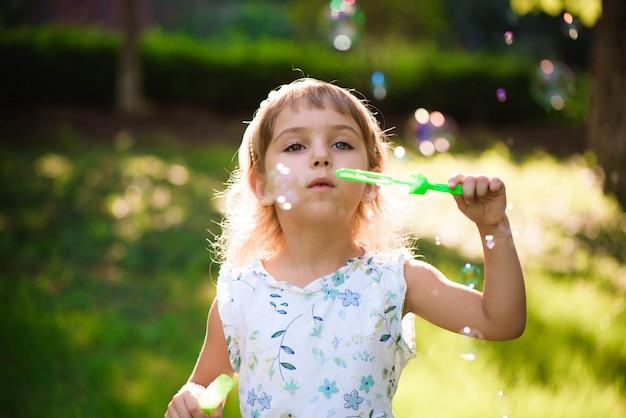 Fille avec des bulles lors d'une soirée d'été ensoleillée