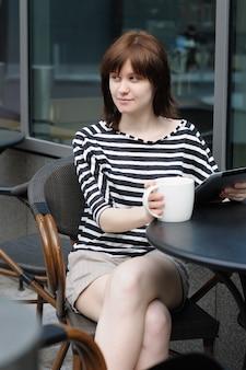 Fille buvant du café et en utilisant une tablette dans un café en plein air