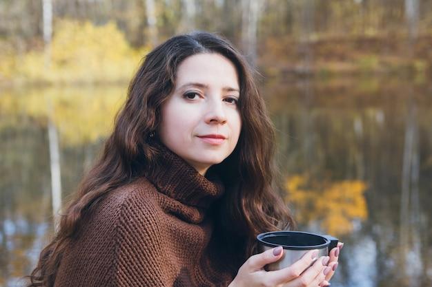 Fille buvant du thé sur un pont en bois sur un lac