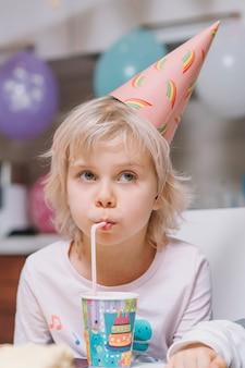 Fille buvant à la fête d'anniversaire