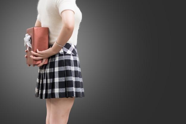 Une fille cache un cadeau pour la surprise présente derrière le dos