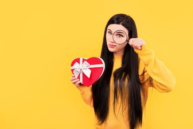 Fille avec un cadeau et une loupe, le concept de recherche d'un cadeau