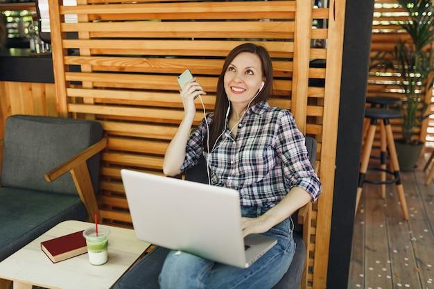Fille calme dans la rue en plein air café d'été café en bois assis avec sur ordinateur portable moderne, téléphone portable