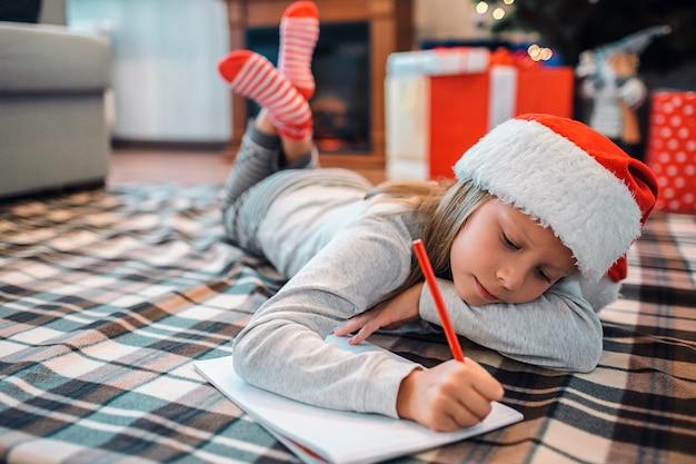 Fille calme et paisible gisant sur le sol et écrivant une lettre.