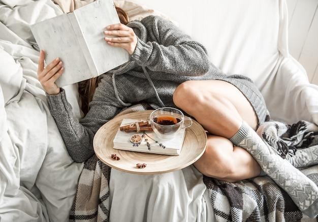 Fille sur le canapé avec du thé et un livre