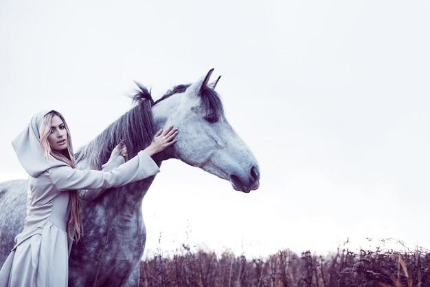 Fille à la cape à capuchon avec cheval, effet de tonifiant