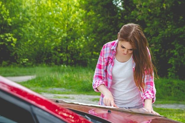Fille avec carte en main debout à côté d'une voiture dans la forêt.