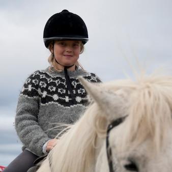 Fille en casque d'équitation à cheval en islandais