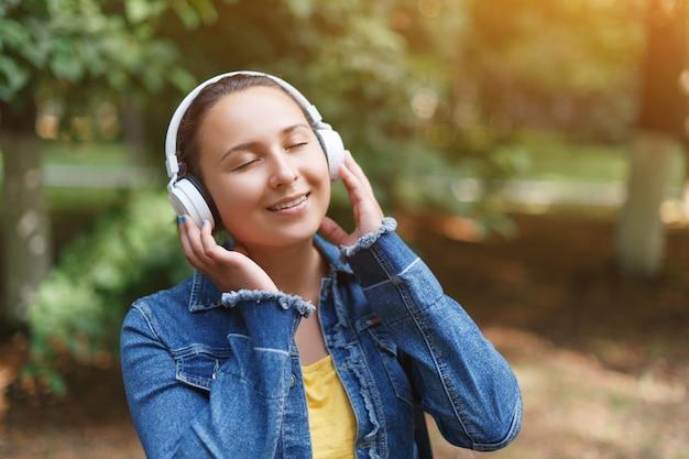 Fille avec un casque marchant dans le parc par une journée ensoleillée et écouter de la musique