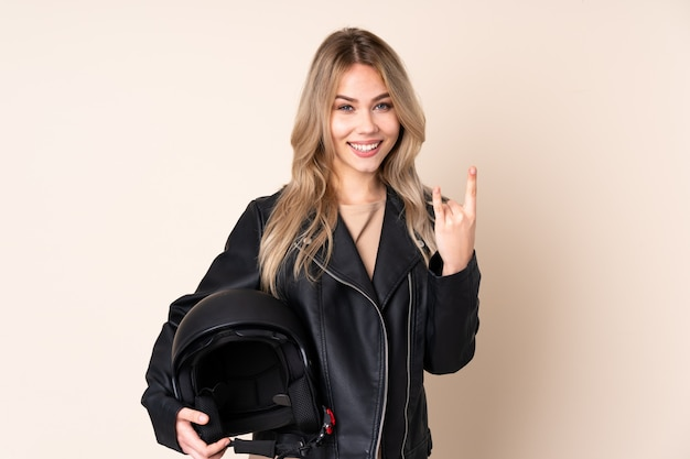 Fille avec un casque de moto sur un mur beige faisant un geste rock