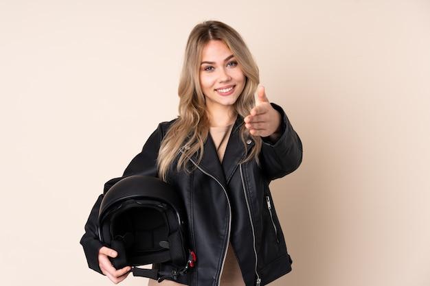 Fille avec un casque de moto sur le mur beige se serrant la main pour fermer une bonne affaire