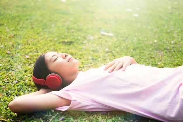 Fille avec un casque sans fil à l'écoute de la musique dans le parc.