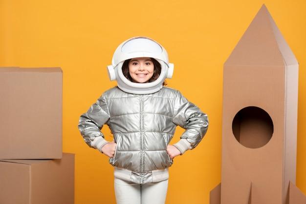 Fille avec casque spatial et navire en carton