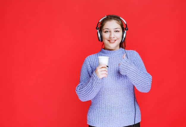 Fille avec un casque tenant une tasse de café et montrant un signe de plaisir.