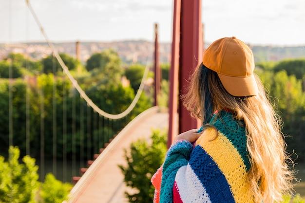 Fille avec casquette, lunettes de soleil, veste de sport dorée et couverture multicolore face au pont rouge à l'aube. concept de mode de vie