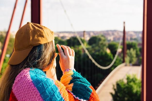 Fille avec casquette, lunettes de soleil, veste de sport dorée et couverture multicolore face au pont rouge à l'aube. regardant le paysage avec des lunettes. concept de mode de vie