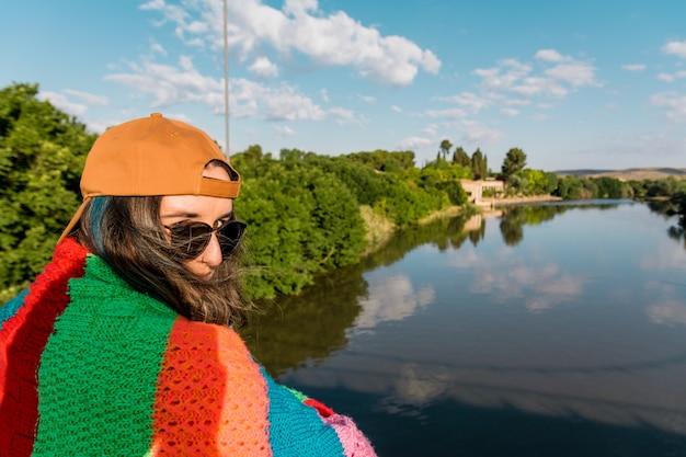 Fille avec casquette, lunettes de soleil, veste de sport dorée et couverture multicolore face à la rivière au lever du soleil. concept de mode de vie