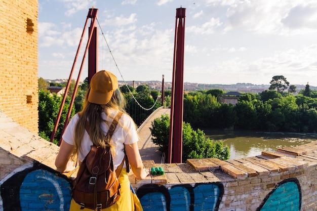 Fille avec casquette, lunettes de soleil, veste de sport dorée et sac à dos en cuir face à la rivière à l'aube. concept de mode de vie