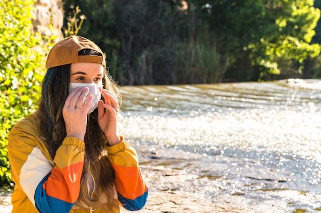 Fille avec casquette, masque, veste de sport dorée, sac à dos en cuir assis sur une couverture multicolore au bord de la rivière. temps de relaxation. concept de mode de vie
