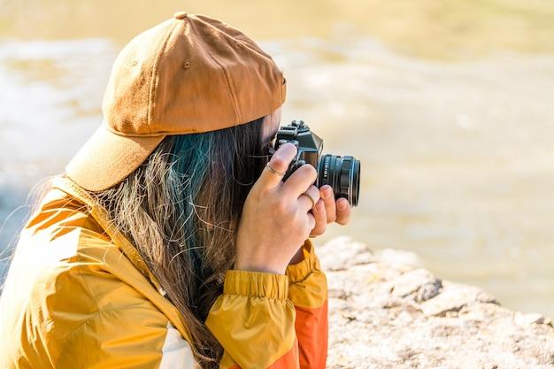 Fille avec une casquette et une veste de sport dorée prenant une photo avec son appareil photo vintage dans la nature. riverfront. concept de mode de vie