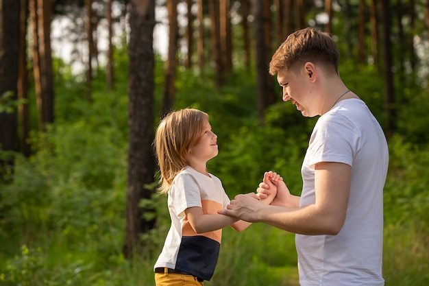 Fille caucasienne de 6 ans tenant la main de papa se regardant dans la forêt. père et fille jouant ensemble, riant et s'amusant. concept d'activité de famille heureuse