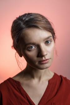 Fille caucasienne assez sensuelle en chemise rouge regardant dans la caméra et en inclinant la tête. portrait de beauté sur fond rose