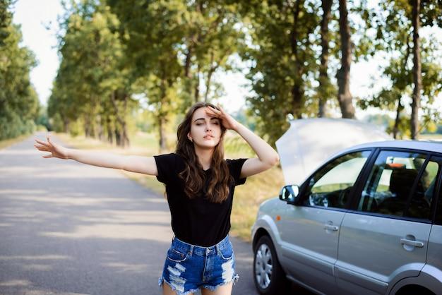 Fille caucasienne déconcertée lève la main pour arrêter d'approcher la voiture et demander de l'aide