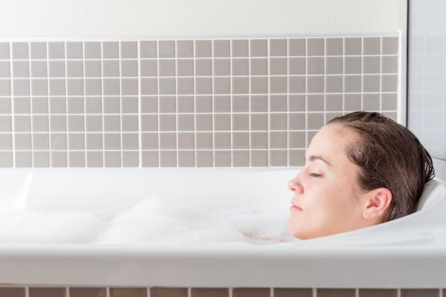Fille caucasienne détendue dans une baignoire avec de la mousse