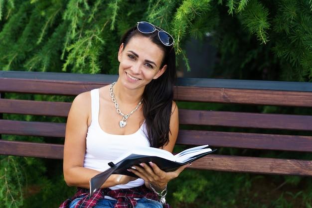 Une fille caucasienne indépendante est assise sur un banc et écrit dans un cahier d'éducation et de concept de journalisme hap...
